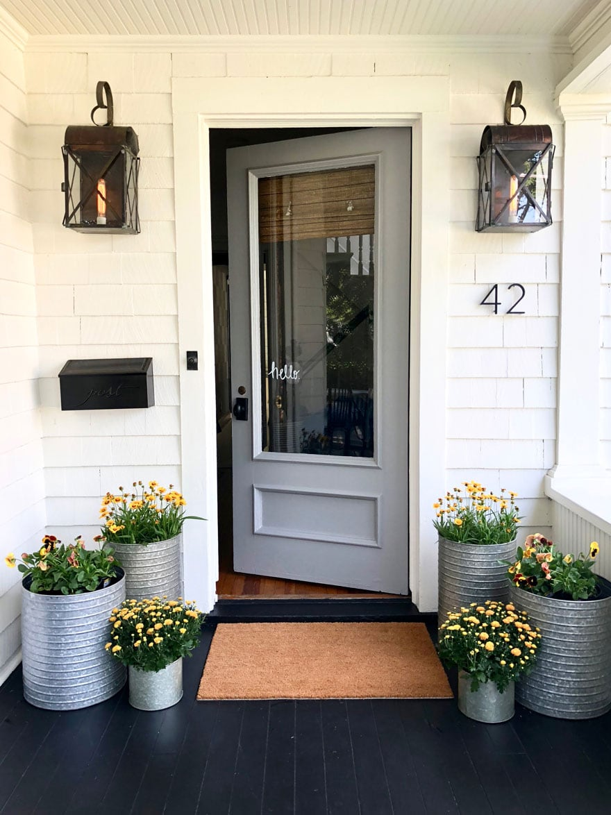 front door on white house with lights and planters