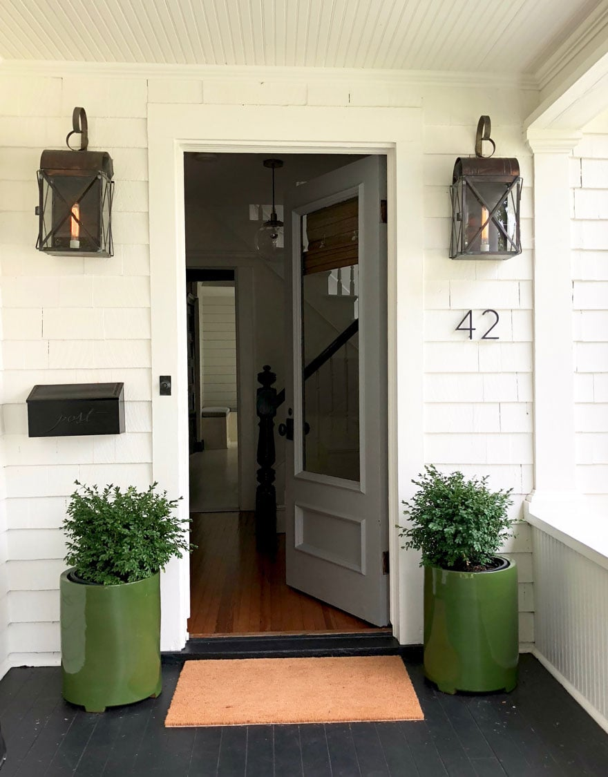 gray front door with planters and boxwoods