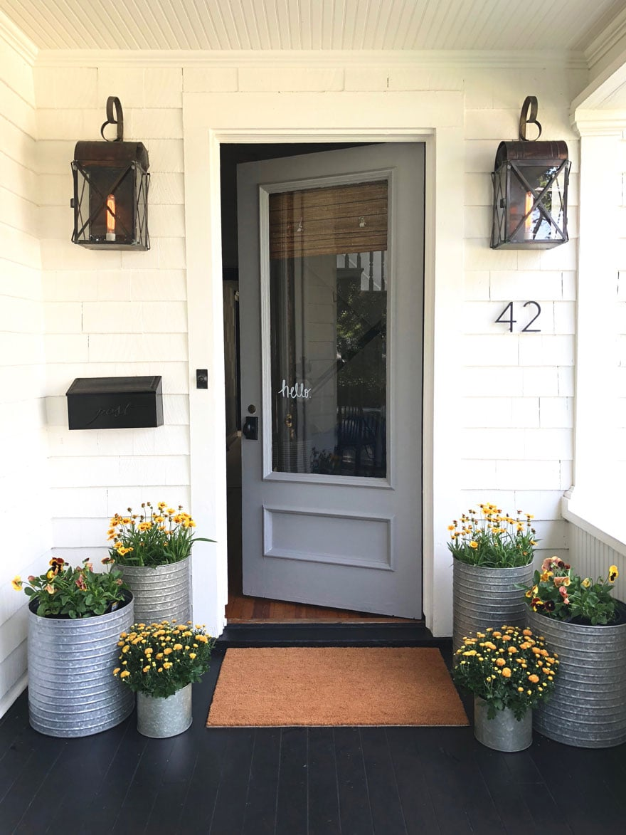 white house, gray door with planters and lanterns