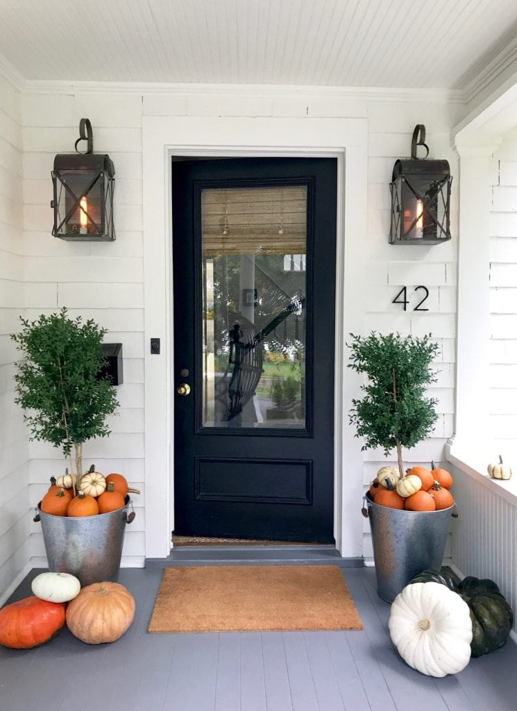 white house with black door with planters and pumpkins