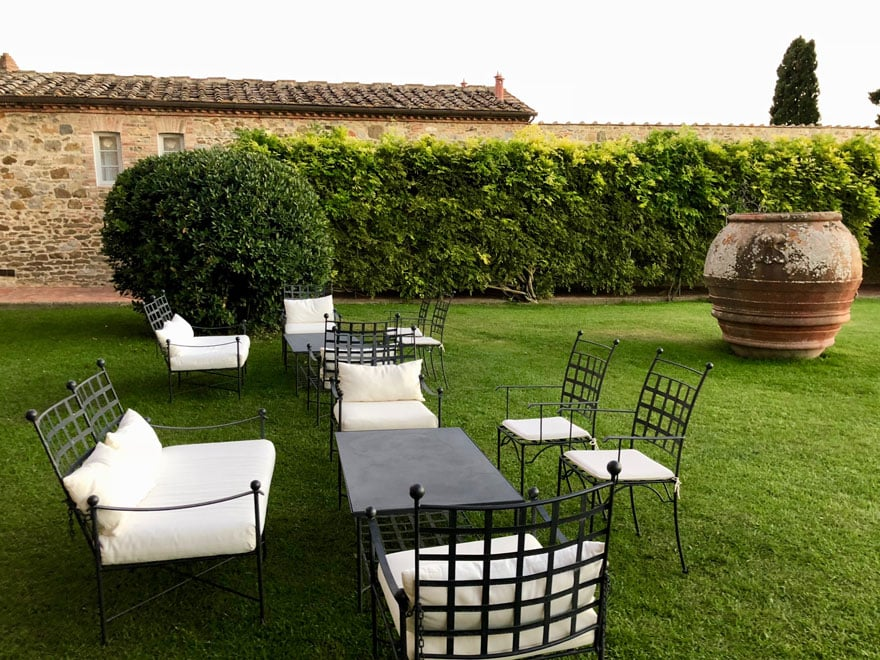 chairs with cushions, grassy area, very large planter, hedges, stone buildings