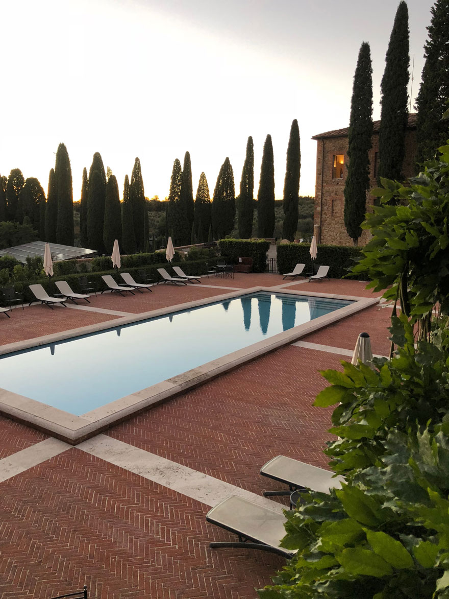 rectangular pool with Italian Cypress trees and red brick