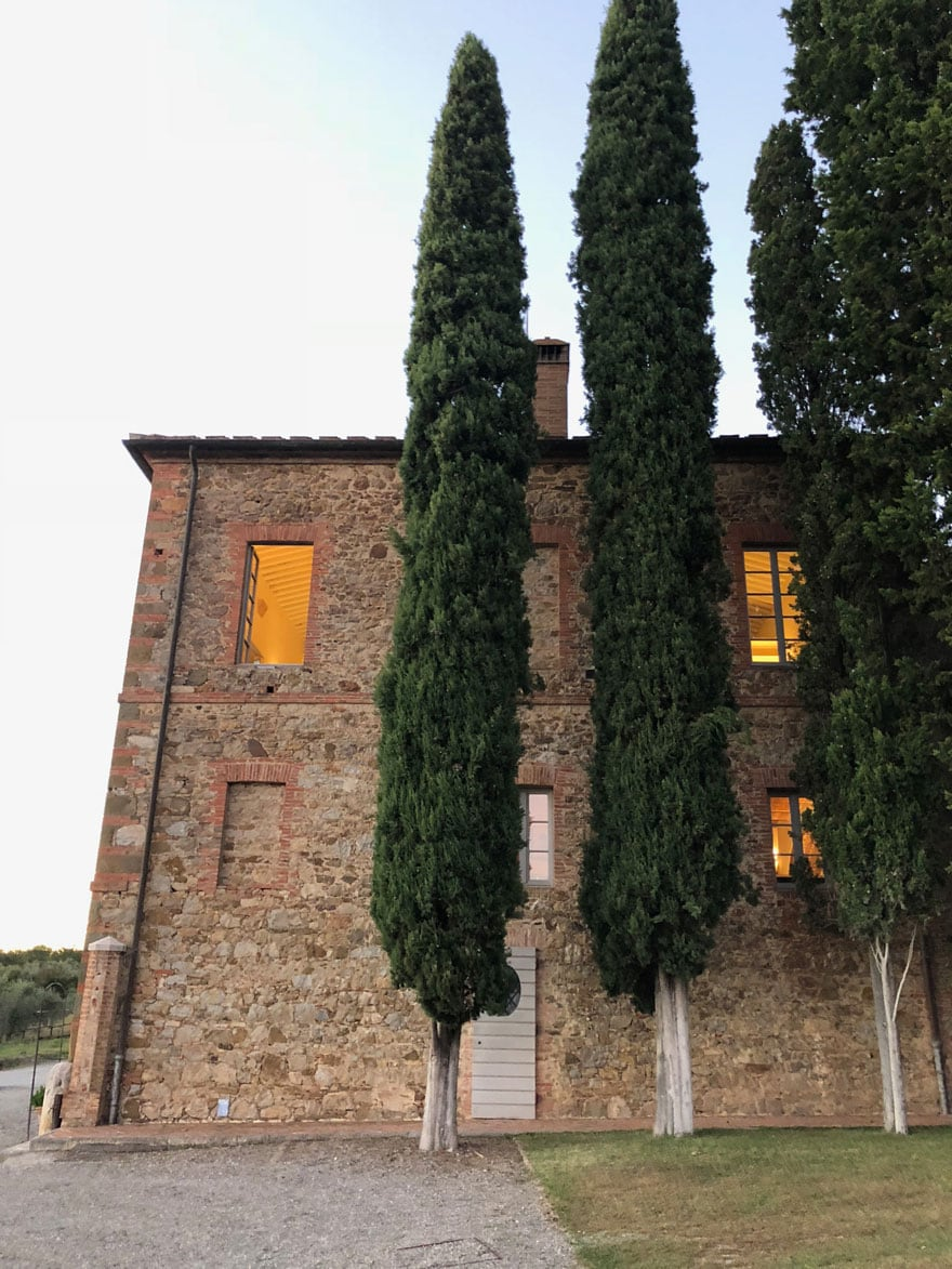 Italian cypress trees against stone building with windows
