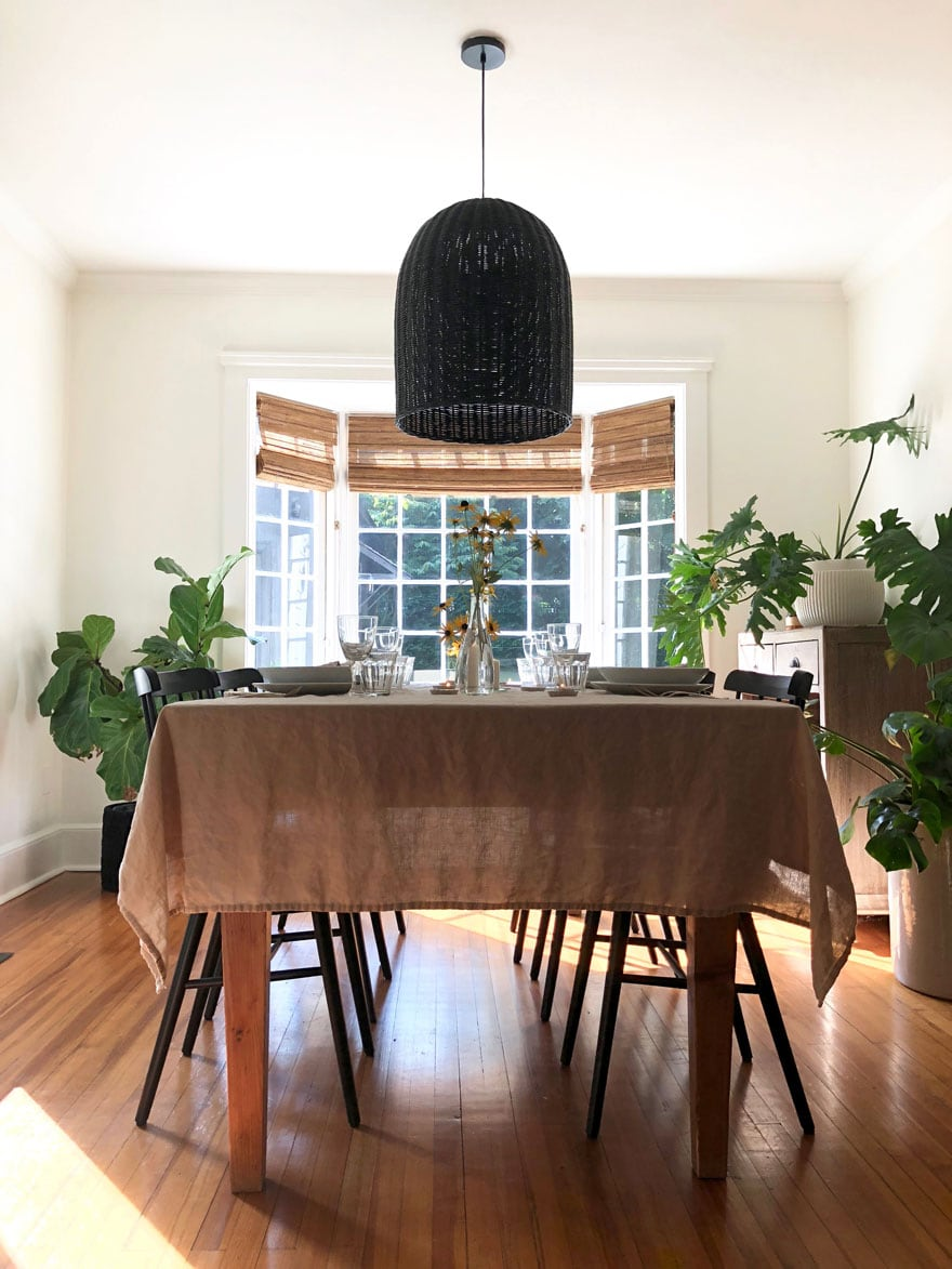 table and chairs with tablecloth and large blaclk pendant in room with large window