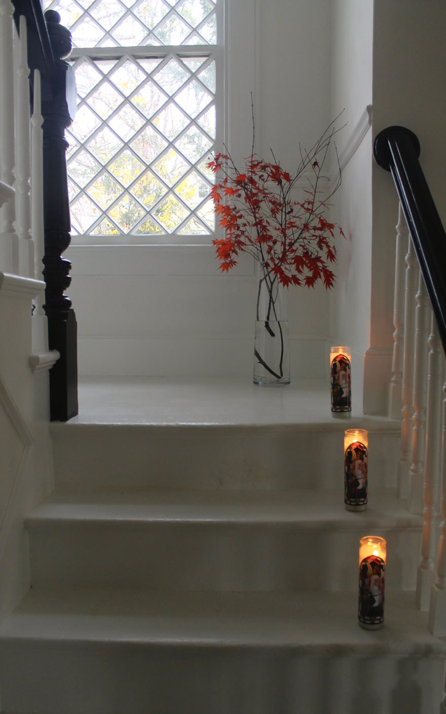 white painted stairs, red leaves in vase, religious candles