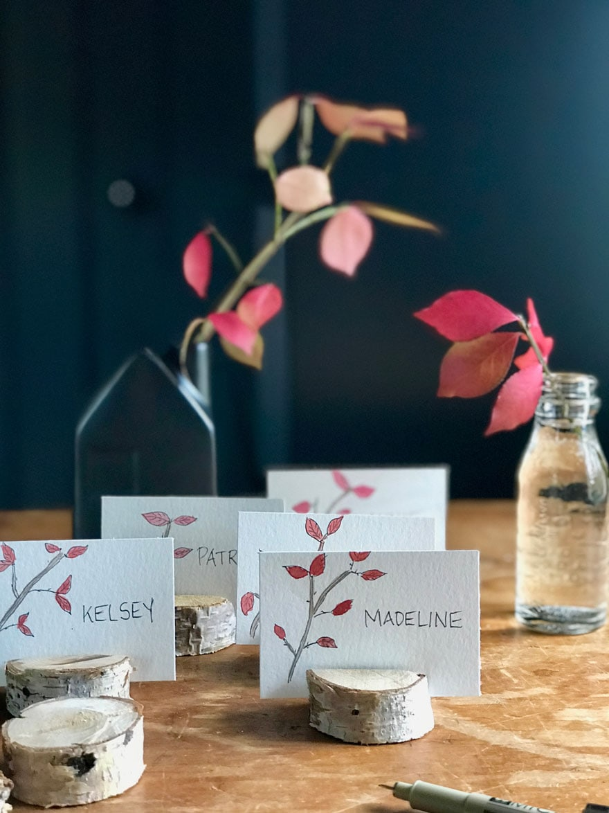 place cards with red branches in small bottle