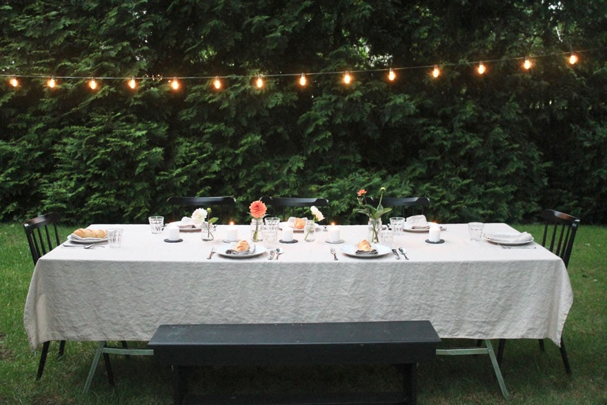 table outdoors under strand of lights against backdrop of trees