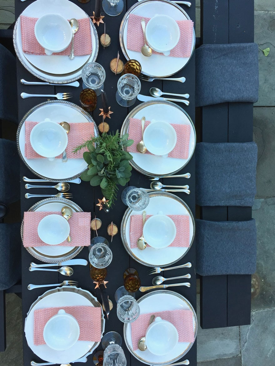 eight place settings on black table with white dishes and herbs as centerpiece