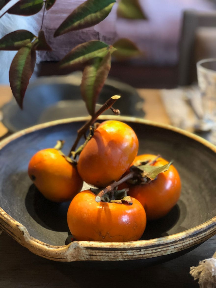 bowl with four persimmons