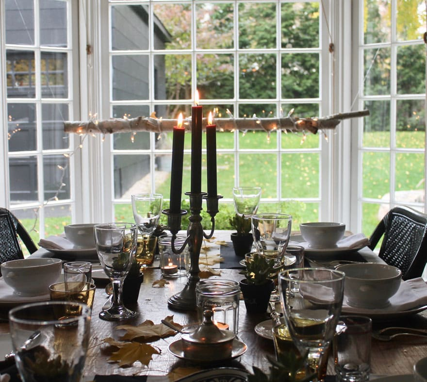 table with dishes, windows overlooking backyard with grass