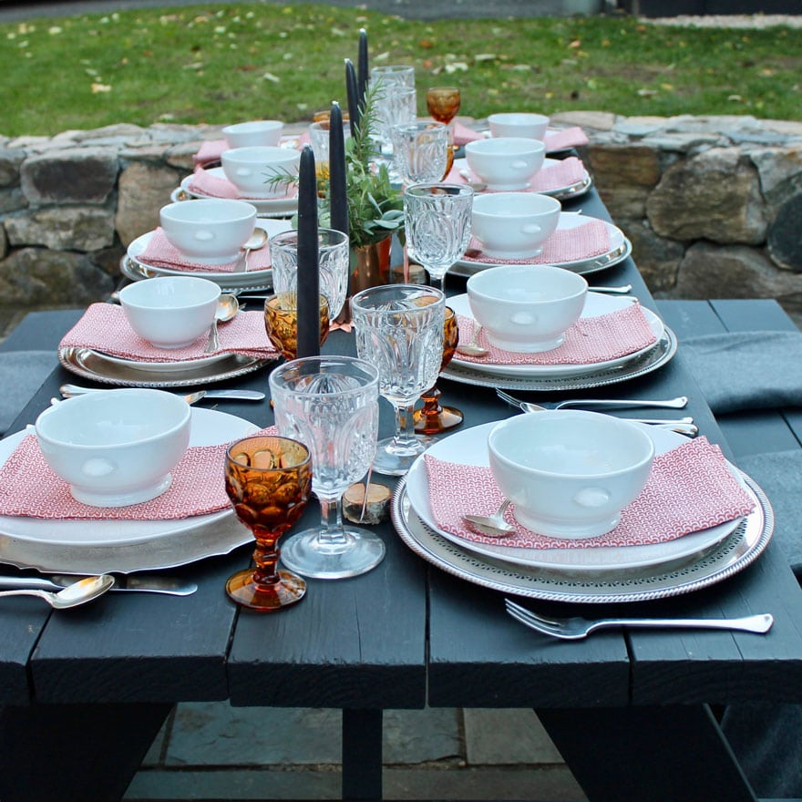 black picnic table with dish, glasses, napkins, candles.