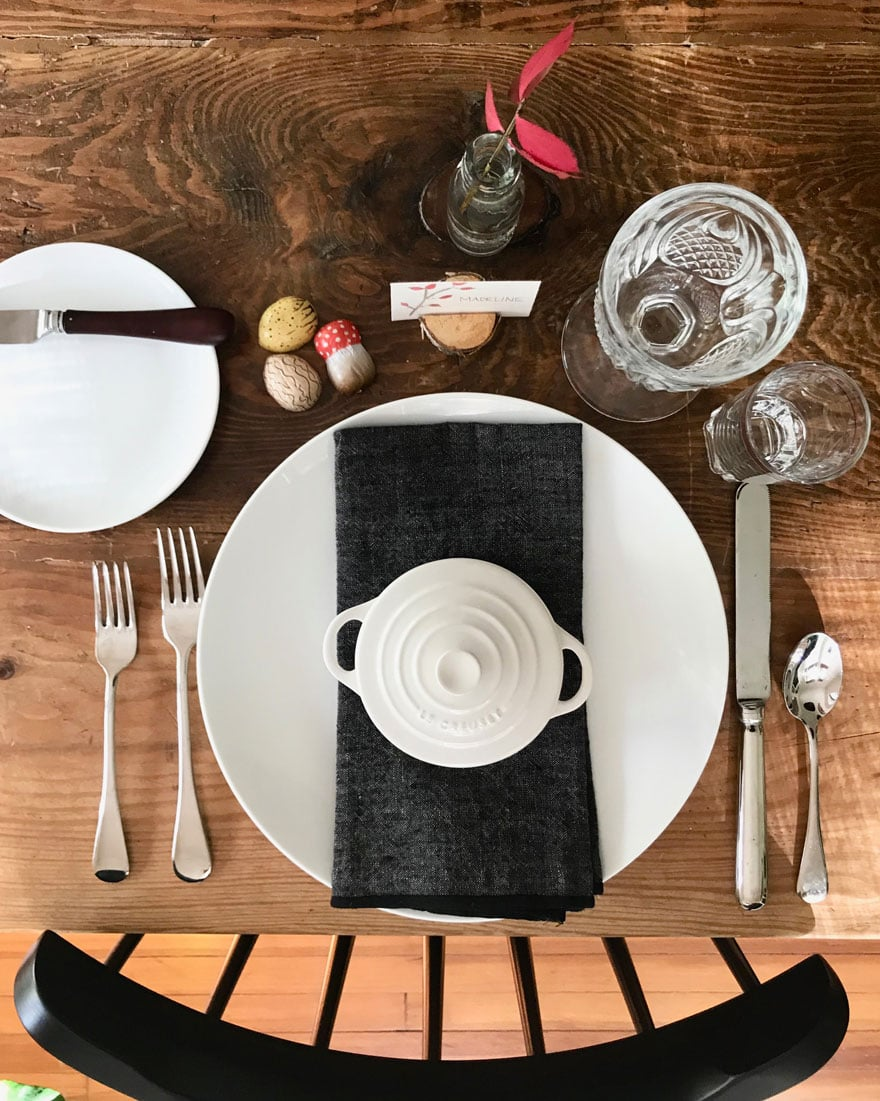 white plate, black napkin, choclolates, glassware on wood table