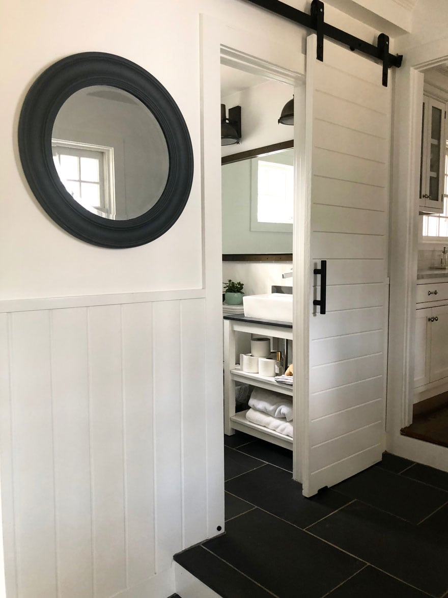 barn door in white bathroom with round mirror