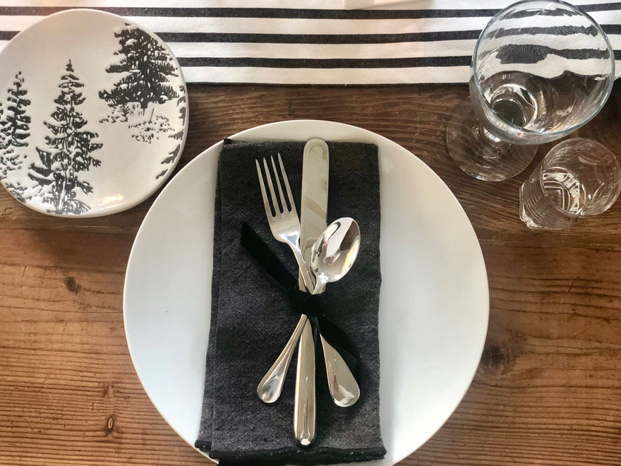 black and white runner, silverware on black napkin tied with ribbon
