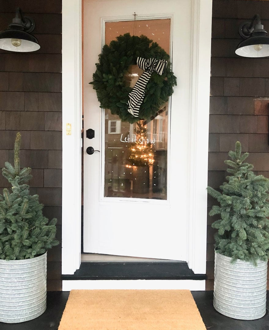 white front door on shingled cottage with trees in planters and wreath on glass door