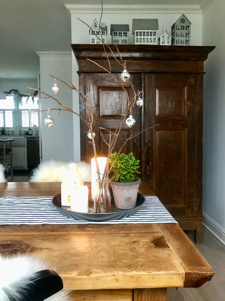 armoire, metal tray with candles and plant on wood table