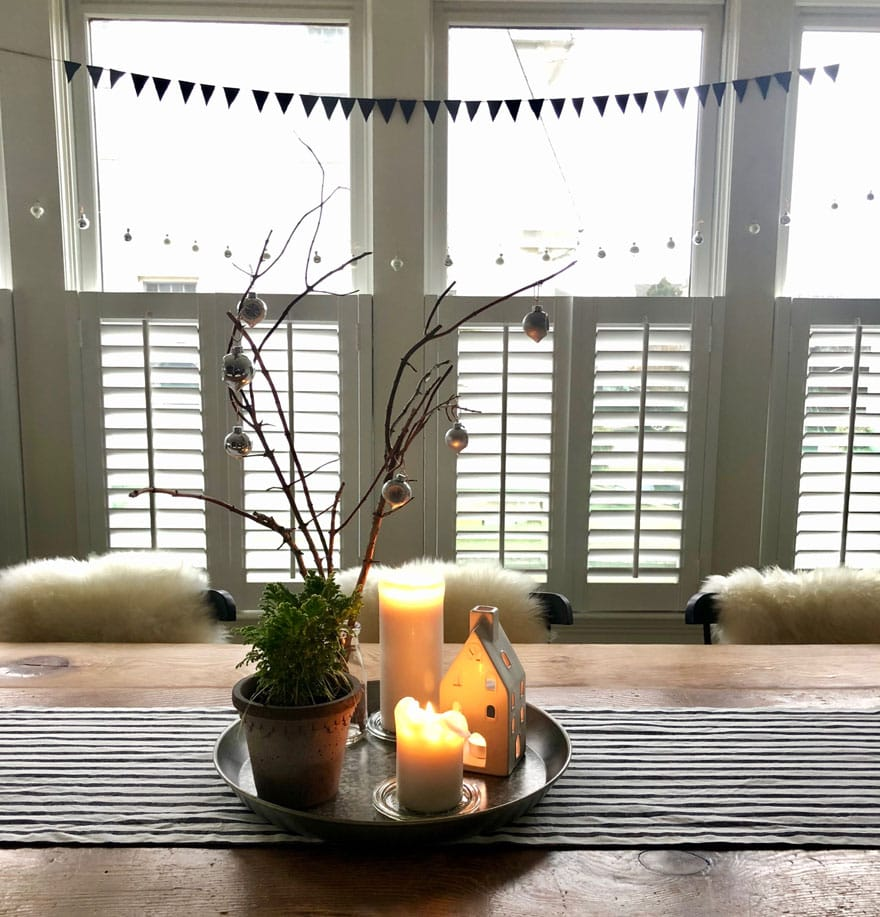 garland, shutters, candles in tray on table