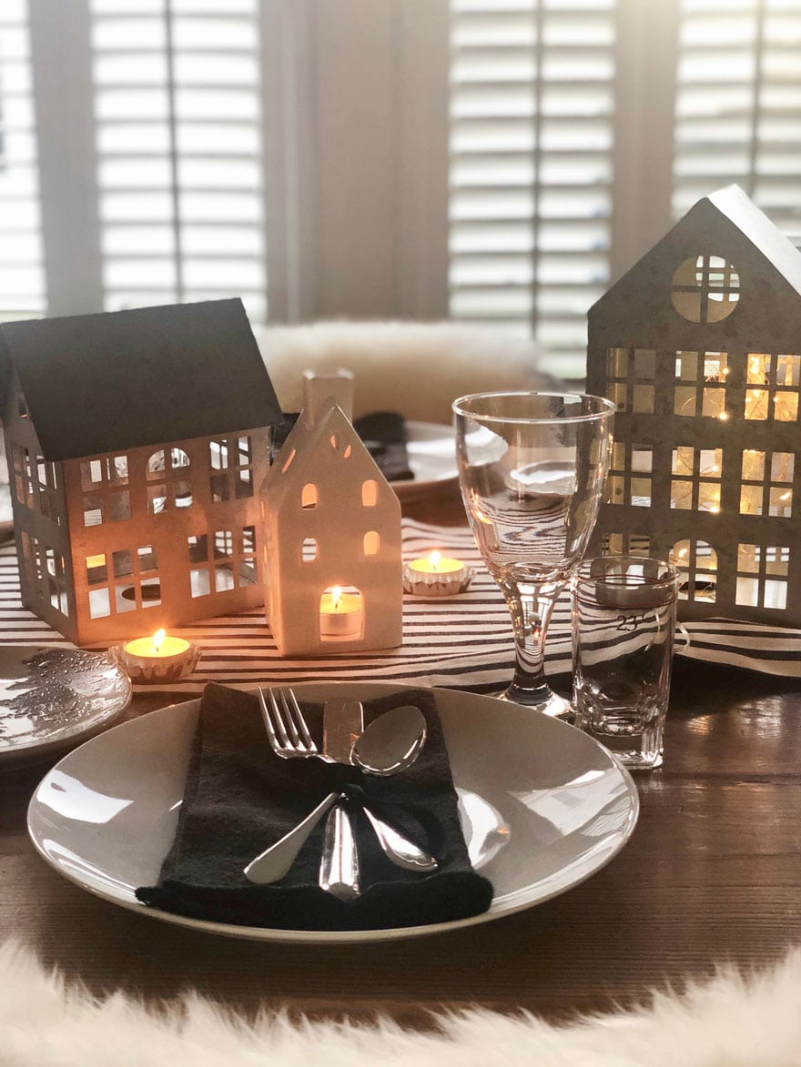 little houses and candles on table with placesettings