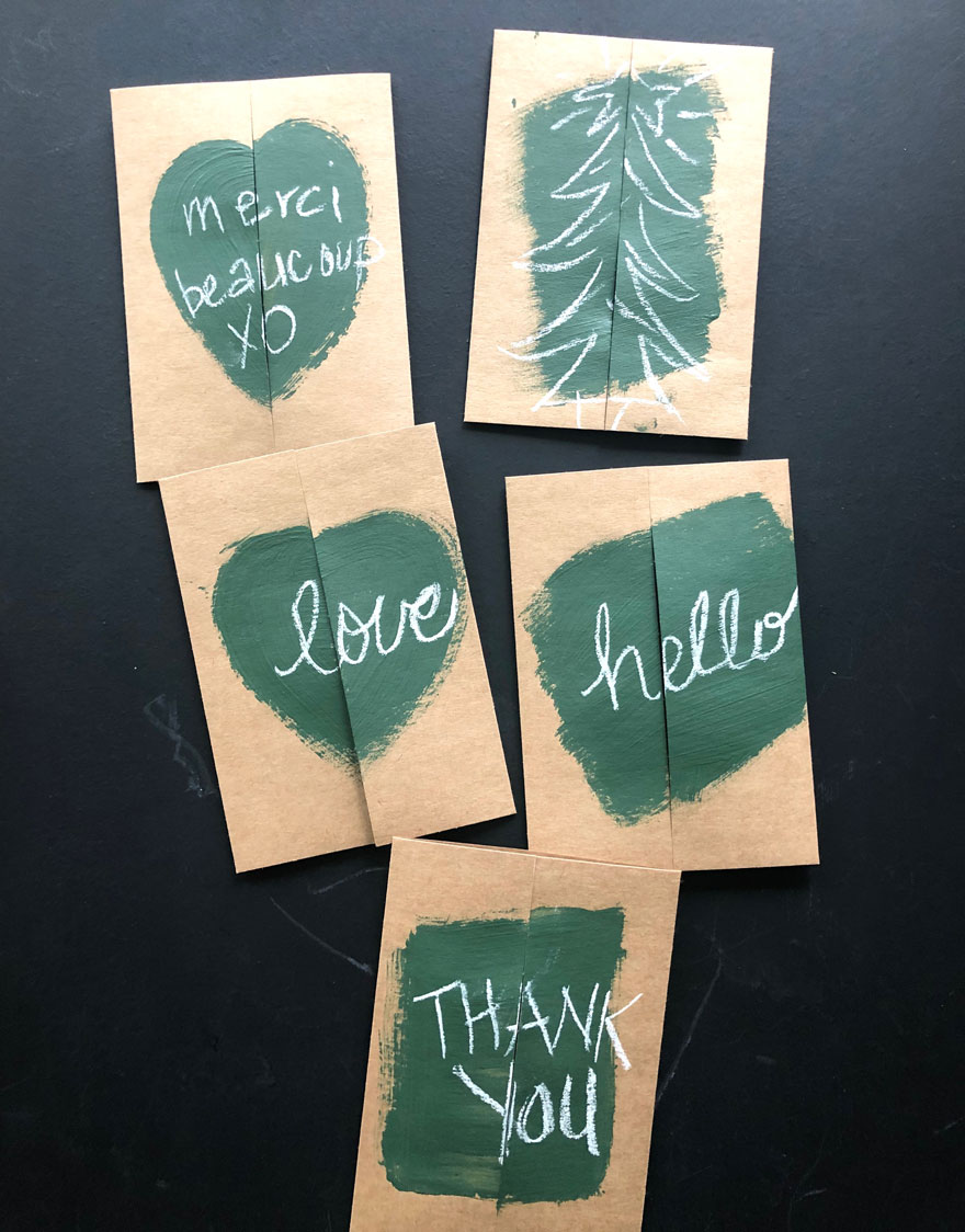 cards with green paint and words in chalk on black background