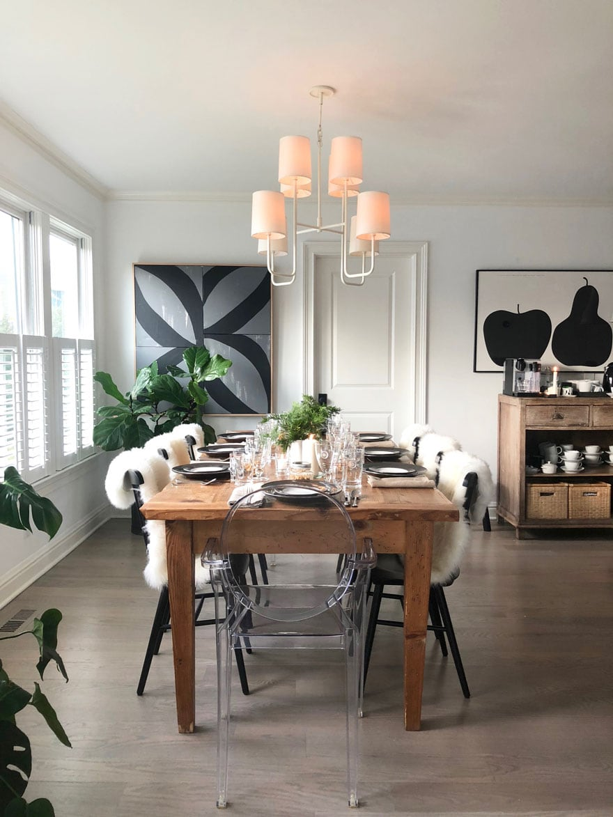 dining room table with place settings in a room with white chandelier and black and gray abstract art