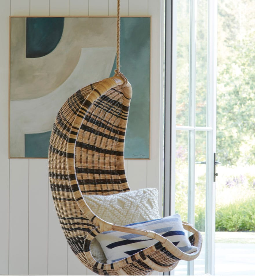 hanging chair with art on panned wall