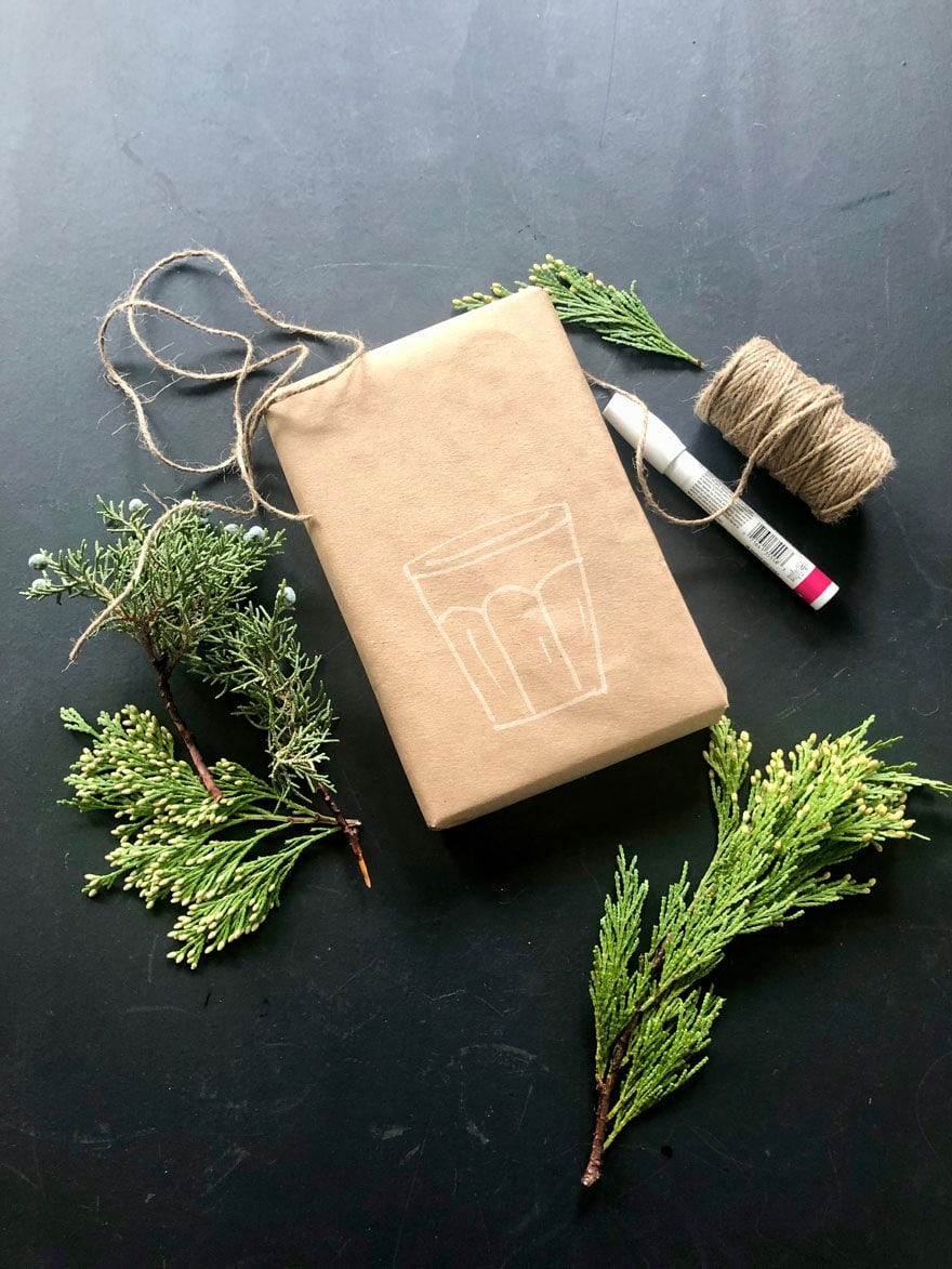 box wrapped in kraft paper with jar drawn and fresh evergreen clippings, twine on chalkboard background