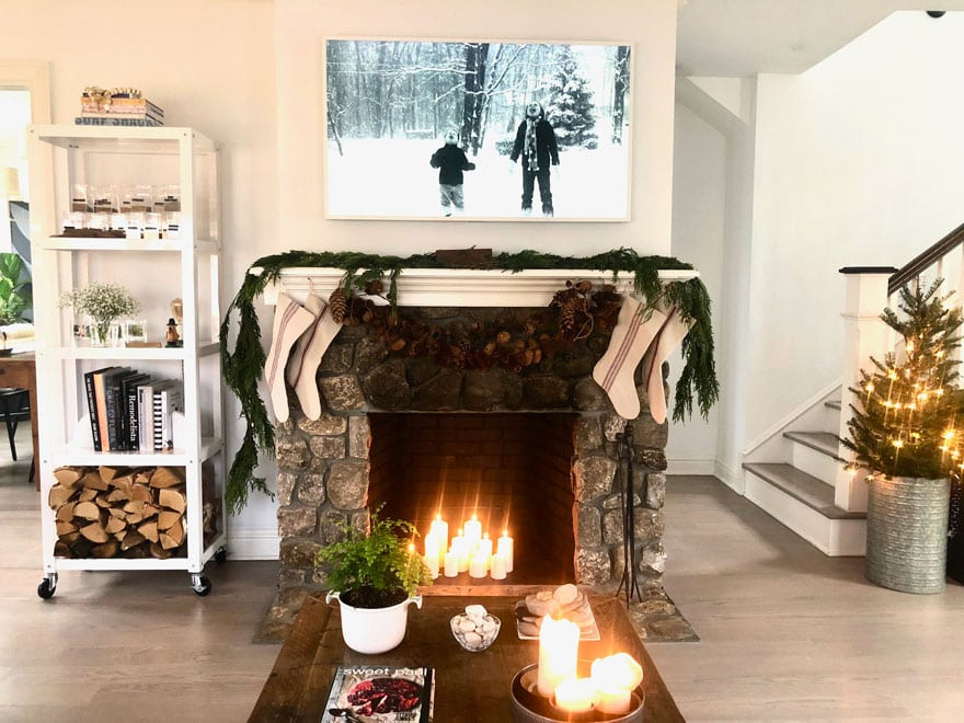 stone fireplace with stockings, greenery, coffee table with candles