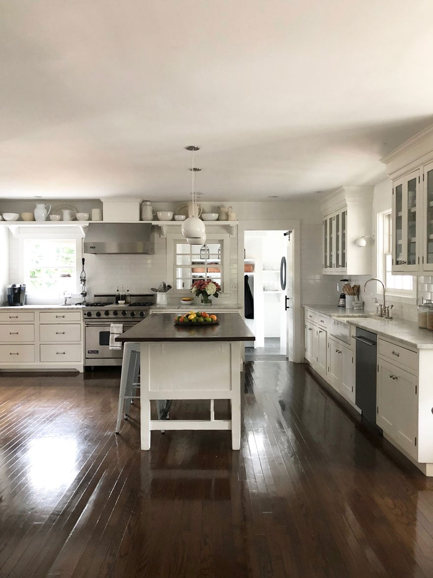 white kitchen, kitchen island, fruit bowl, dark wood floors