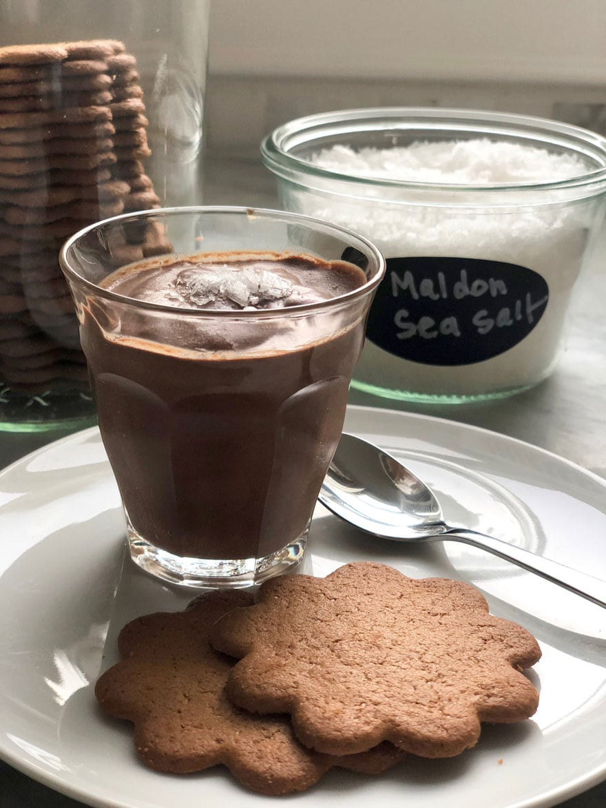 glass with chocolate mousse, plate, spoon, cookies, salt in glass container