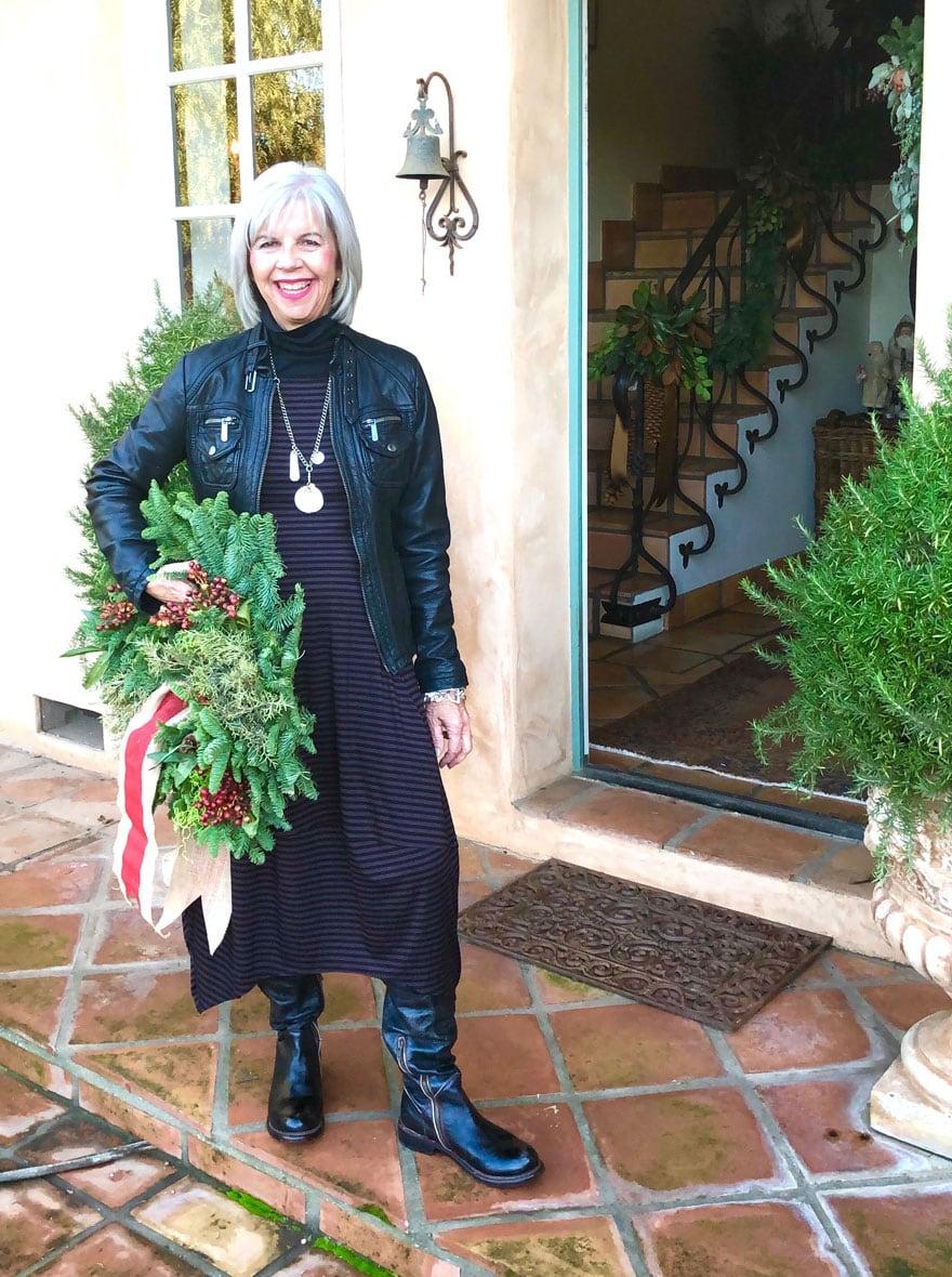 woman holding wreath in front of open door