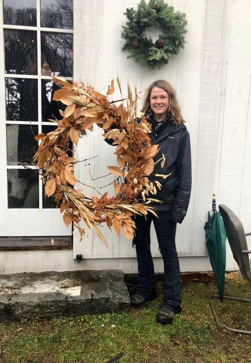 Woman standing in front of white barn holding a wreath