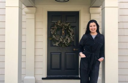 woman standing at front door with wreath