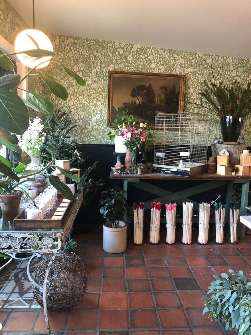 shop with candles, red tiel floor, patterned green wallpaper