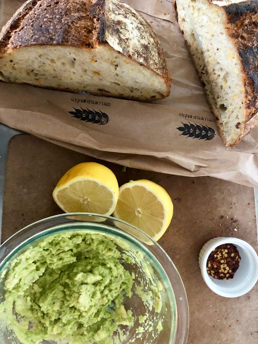 bread on bag, lemon, red pepper, avocado in bowl