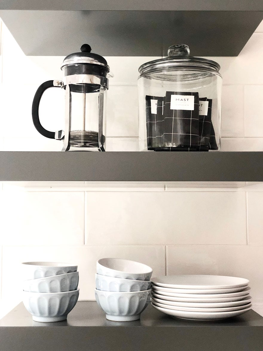 shelves with jar of candy bars, small latte bowls, coffee press, plates