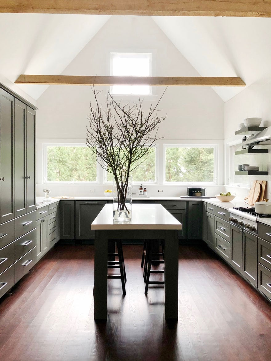 kitchen with island and stools, branches in vase, windows