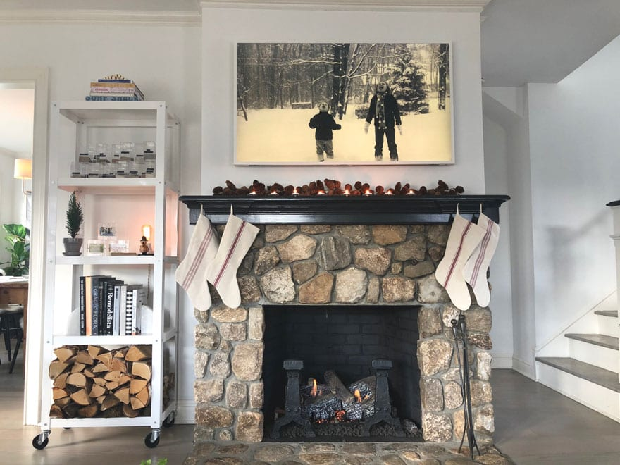 fireplace with stockings, tall shelf, black and white photo