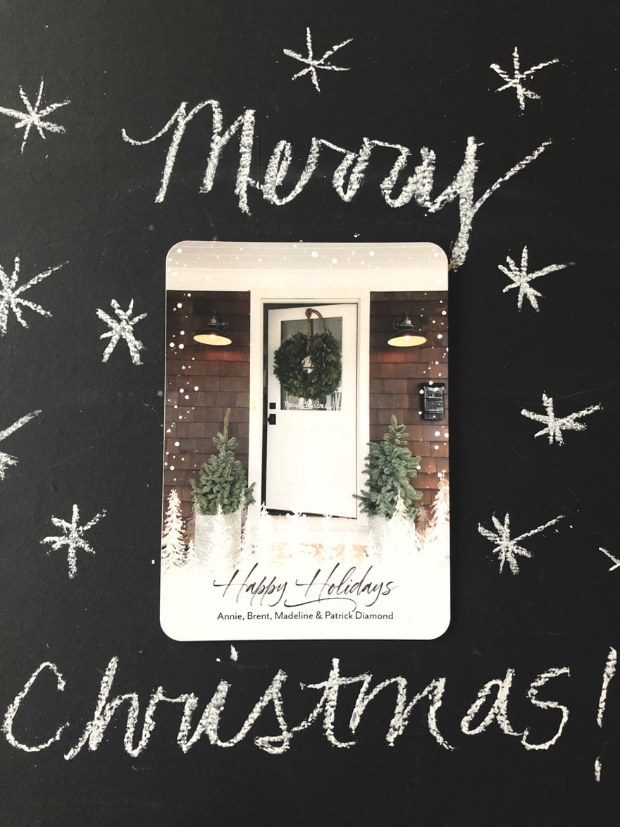 holiday card on black chalkboard background with merry Christmas in chalk with snowflakes in chalk