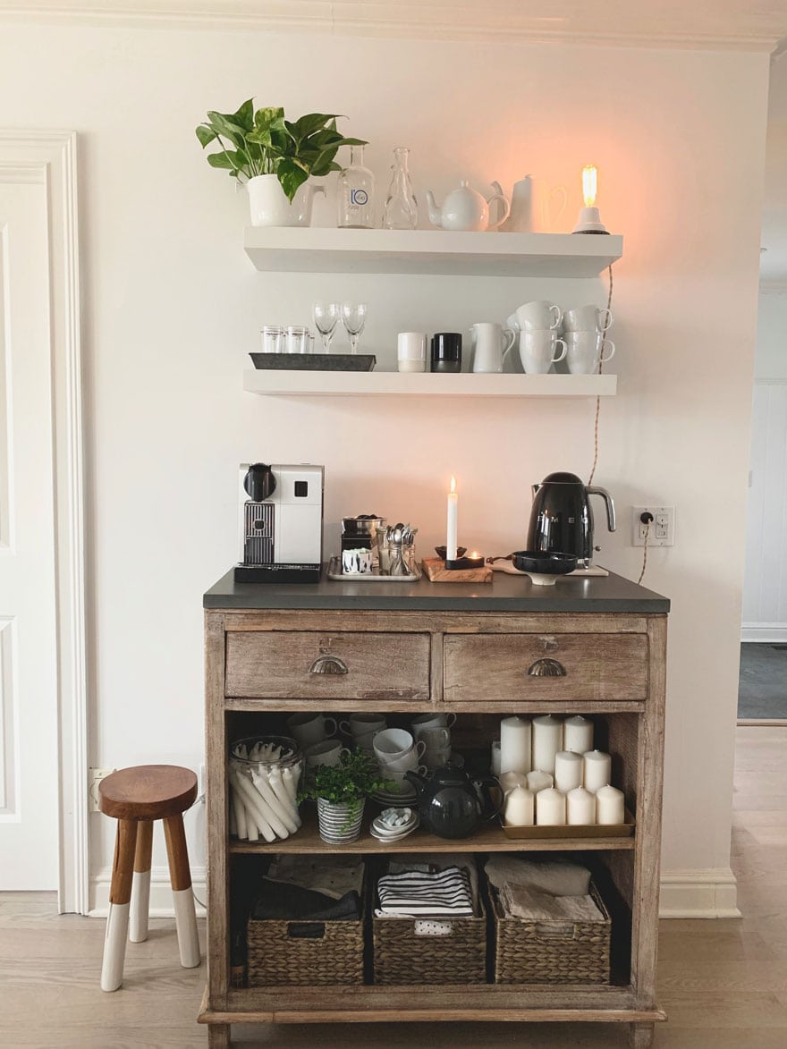 open shelves, furniture with stone top and coffee items, stool, candles