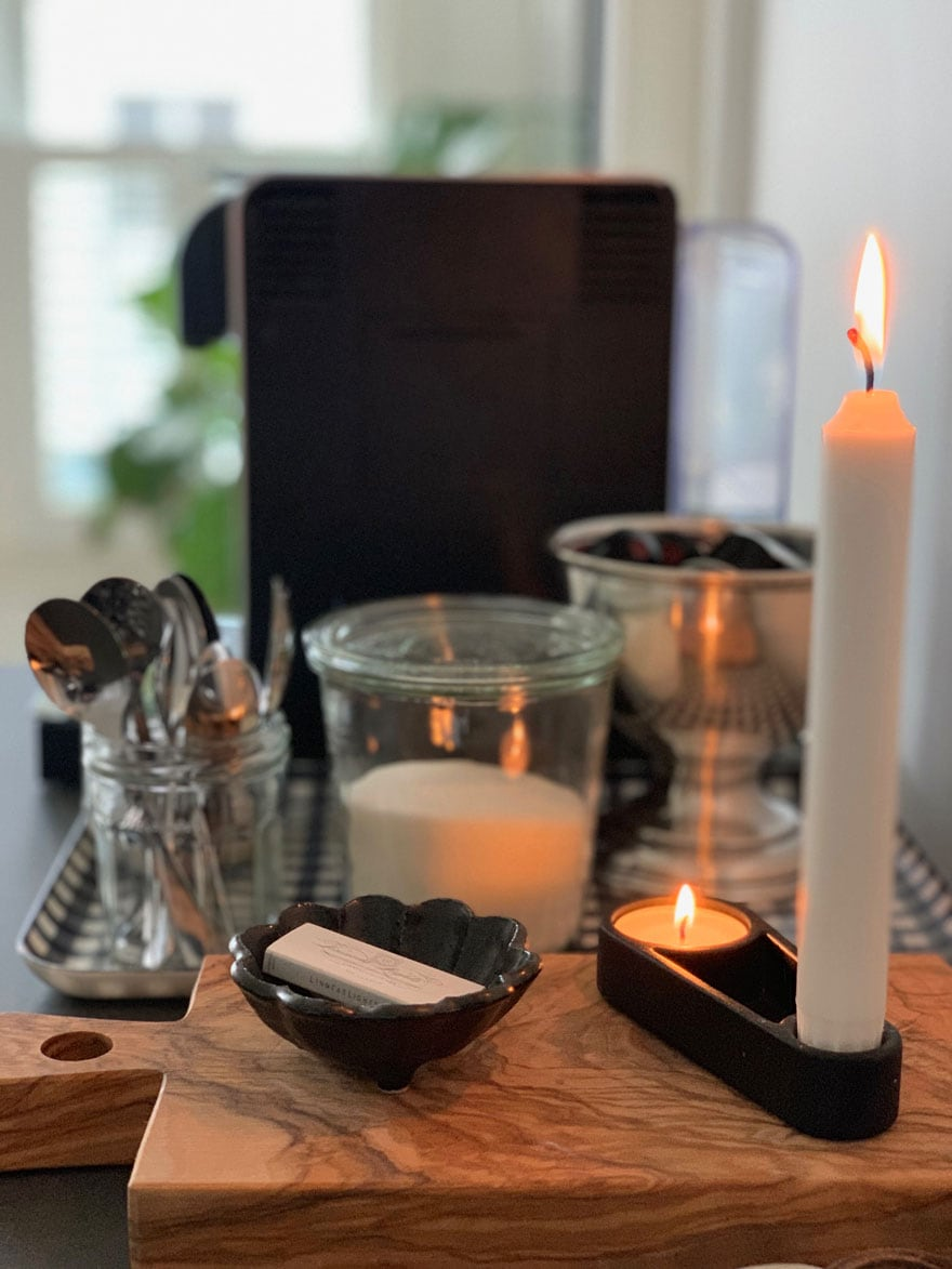 coffee maker, candle, wood cutting board. matches in small dish