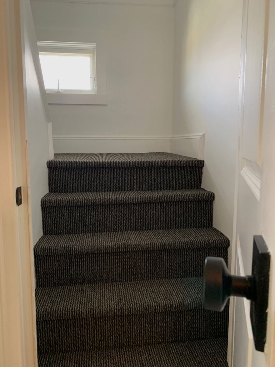 white door with black hardware and carpeted steps