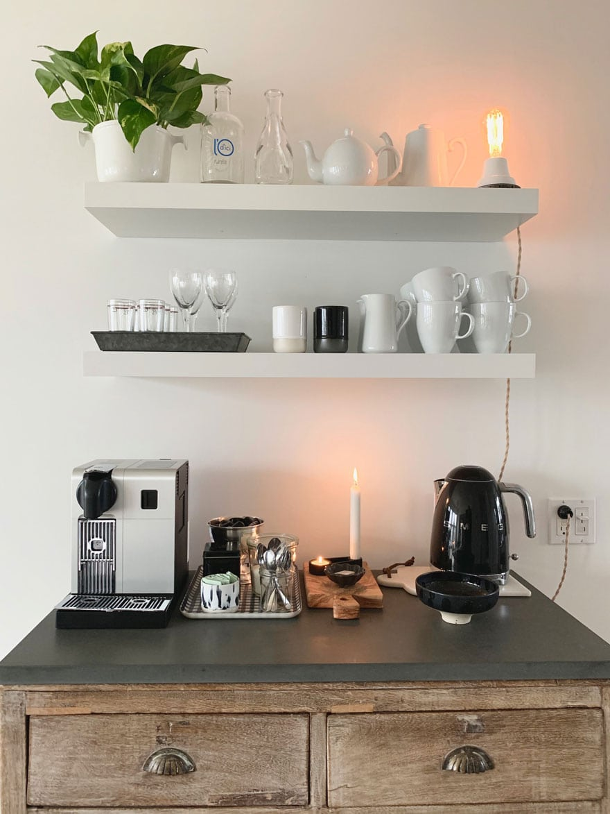 white shelves with plant, tea pot, coffee maker on stone