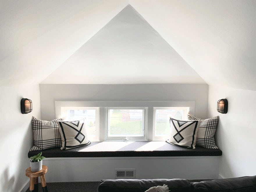window seat under 3 square windows, pillows, stool, small plant, sconces