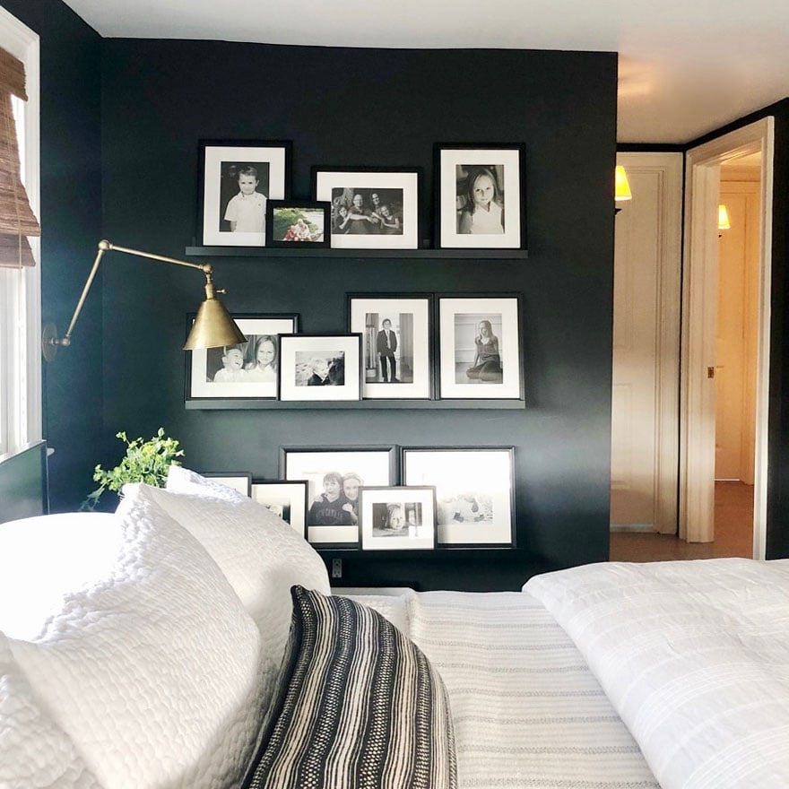 black and white photos on black wall on ledge shelves