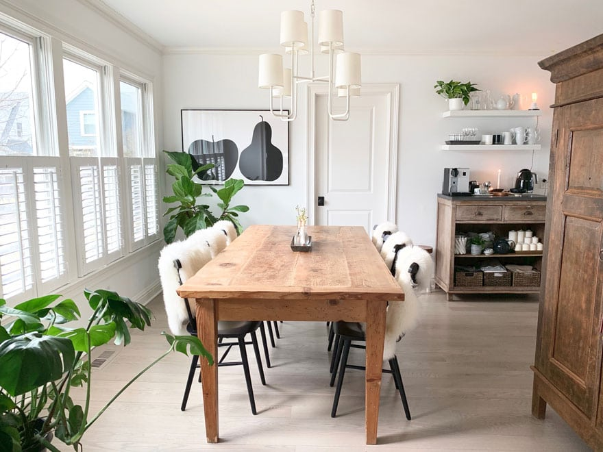 farm table with black chairs with sheepskins