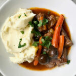 beef stew in bowl with mashed potatoes and fresh parsley