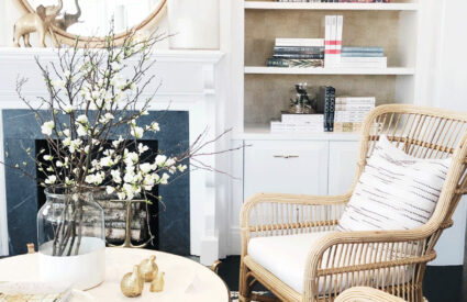 fireplace with round mirror above, rattan chairs, spring branches on large round coffee table, bookshelves