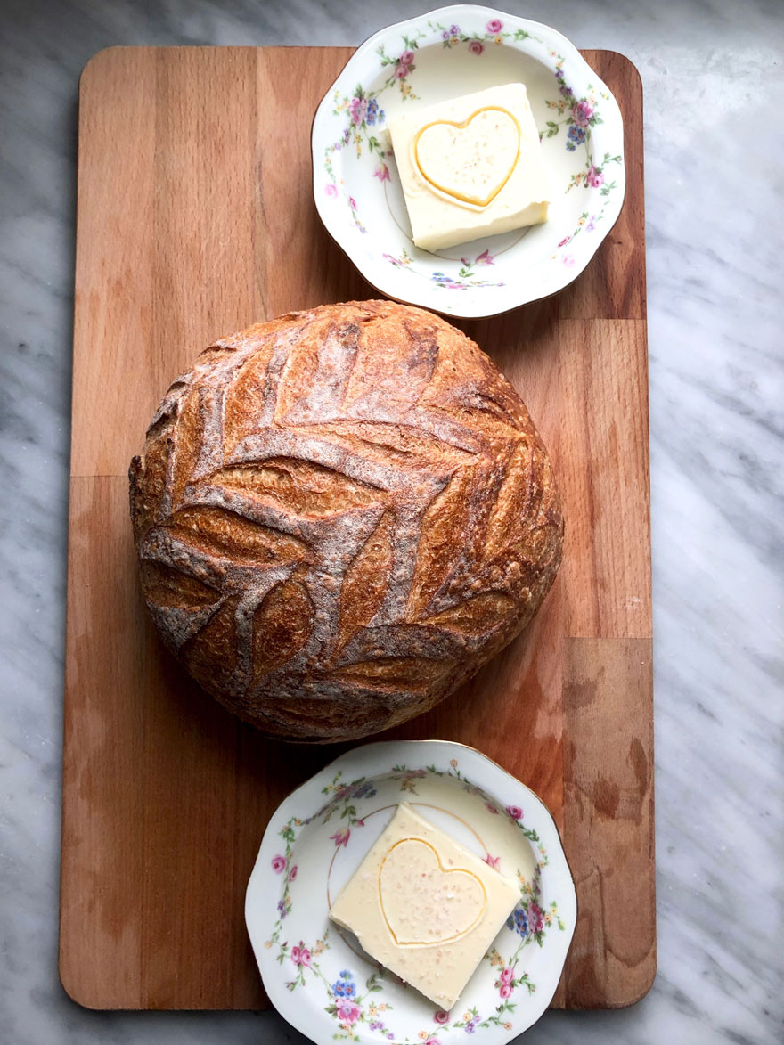 round bread on board with two bowls with salt