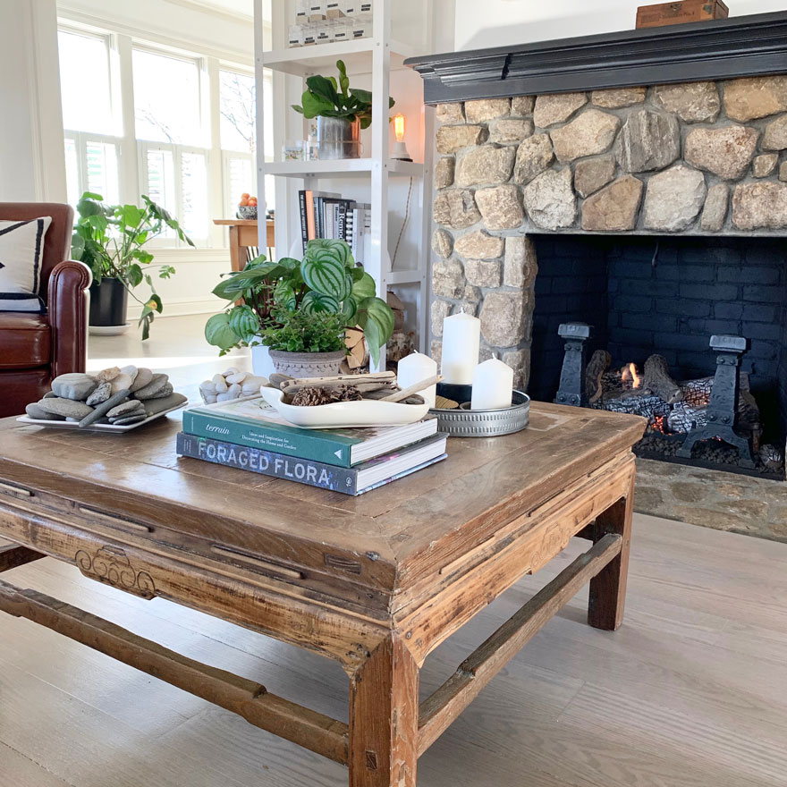 coffee table with books, rocks, stones, candles, tray, plants, stone fireplace in background, chair