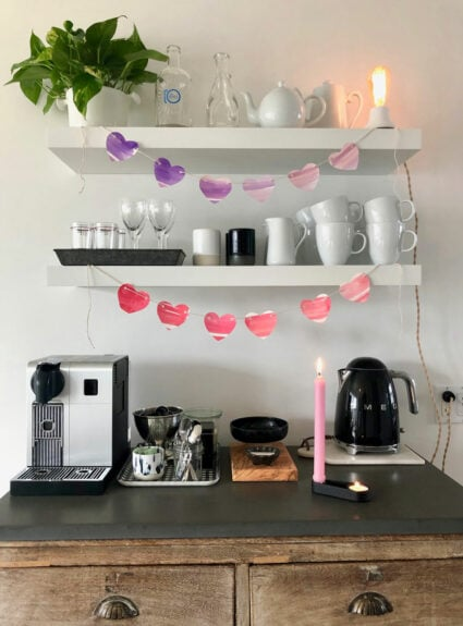 coffee bar with heart garland, cups, glasses, tea pot, coffee maker, candle